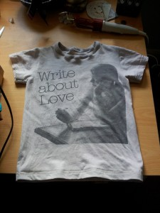"Cut-down pink Belle and Sebastian T-shirt, picture of girl writing with ""Write About Love"" caption."