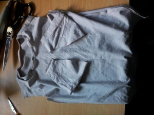 Body of toddler T-shirt, sleeves separately resting on it, with pair of scissors nearby