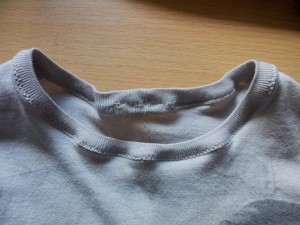 Close-up of neckband of pink toddler T-shirt, slightly puckered