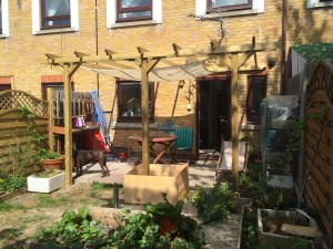 With shade sail and potting table up. Herbs are just visible behind the deckchair, between the mini greenhouse and the back door.